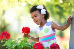 Zwarte meisjes ruikende bloemen stock afbeeldingen
