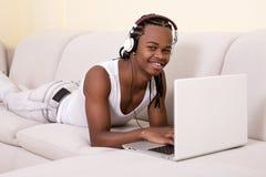 Zwarte mens bij laptop in hoofdtelefoons Stock Afbeelding