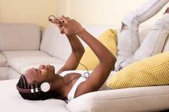 Zwarte mens die in hoofdtelefoons smartphone doorbladeren Stock Afbeelding