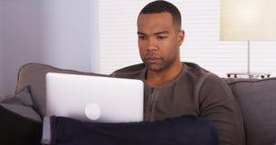 Zwarte mens die laptop op laag met behulp van stock foto's