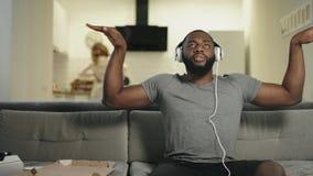 Zwarte mens die thuis met het toenemen handen dansen Grappige kerelzitting in hoofdtelefoons stock video