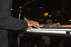 Zwarte mens die in zwart kostuum het toetsenbord spelen bij nacht met bokehachtergrond - bewegingsonduidelijk beeld stock foto