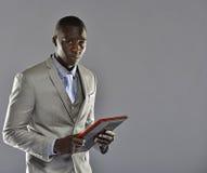 Zwarte mens in een de tabletcomputer van de kostuumholding Royalty-vrije Stock Fotografie