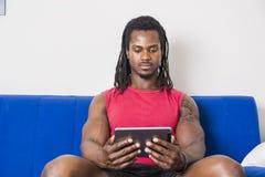 Zwarte mens het letten op film op tabletpc Royalty-vrije Stock Foto's