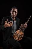 Zwarte mens met etnisch muzikaal instrument royalty-vrije stock afbeelding