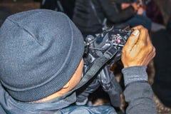 Zwarte mens met gebreid GLB die prestaties videotaping die bij nacht - van over zijn schouder wordt geschoten die camera kenmerke royalty-vrije stock afbeelding