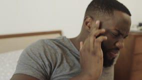 Zwarte mens met hoofdpijn in de ochtend Jonge mannelijke persoon die tempel wrijft stock footage