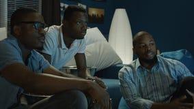 Zwarte mensen die op sporten letten en weddenschappen maken stock video