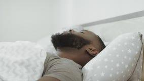 Zwarte mensenslaap in bed in ochtend Jong volwassen behandelend hoofd met hoofdkussen stock videobeelden