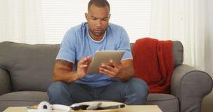Zwarte mensenzitting op laag die tablet gebruiken royalty-vrije stock foto