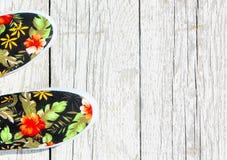 Zwarte met bloementennisschoenen op een witte houten achtergrond De hoogste mening van de zomerschoenen Stock Foto's