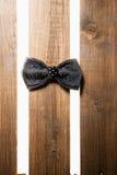 Zwarte met de hand gemaakte vlinderdas over hout Stock Foto's
