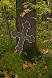 Zwarte met het grijze Orthodoxe kruis van het randmozaïek op een oude de herfstbegraafplaats royalty-vrije stock fotografie