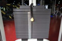 Zwarte metaal of ijzer zware die platen voor sport, oefening, gewichtsmachine met kilogram en pondaantallen worden gestapeld in f Stock Fotografie