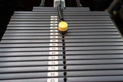 Zwarte metaal of ijzer zware die platen voor sport, oefening, gewichtsmachine met kilogram en pondaantallen worden gestapeld in f Stock Afbeelding