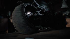 Zwarte motorfiets met groot wiel in de garage bij nacht ghostbike stock videobeelden
