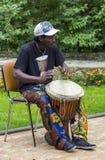: Zwarte musicus van Afrika demostrates hoe te om de trommels te spelen Stock Foto