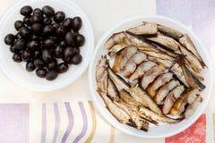 Zwarte olijven en plaat met vissen Stock Fotografie