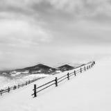 Zwarte omheining op witte sneeuw op bergen stock afbeeldingen