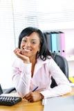 Zwarte onderneemster bij bureau in bureau Stock Foto's