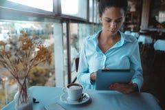 Zwarte onderneemster in koffie met digitale tablet stock afbeeldingen