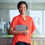 Zwarte ondernemer die bij camera glimlachen terwijl status in bedrijfszitkamer royalty-vrije stock foto