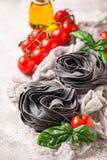 Zwarte ongekookte deegwaren met tomaat en basilicum stock fotografie