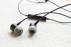 Zwarte Oortelefoon of oortelefoons op witte achtergrond Zwarte oortelefoons Stock Fotografie
