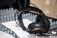 Zwarte oortelefoons op een console in een opnamestudio Stock Fotografie