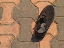 Zwarte oude en uitgeputte schoen op baksteenvloer Stock Afbeelding