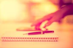 Zwarte pen op het notitieboekje, met achtergrondonduidelijk beeld Stock Foto