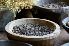 Zwarte peper in een houten kom Stock Foto