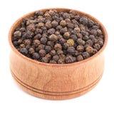 Zwarte peper in een houten kom Stock Foto's