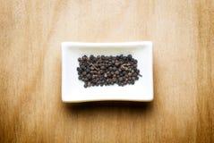 Zwarte peper op houten lijst Stock Foto's