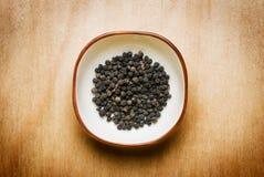 Zwarte peper op houten lijst Stock Fotografie