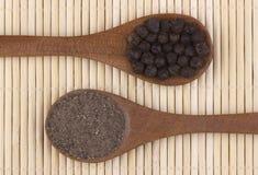 Zwarte peperkorrels en zwarte peperpoeder Stock Afbeeldingen