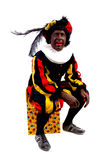 Zwarte piet ( black pete) typical Dutch. Character part of a traditional event celebrating the birthday of Sinterklaas in december over white background sitting Stock Photos