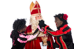 Zwarte Piet giving pepernoten (cookies) to Sinterklaas Stock Photography