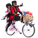 Zwarte Pieten are bringing presents. Zwarte Piet (Black Pete) is a character, part of a  Dutch tradition called Sinterklaas, which is celebrated at December the Stock Image