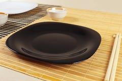 Zwarte plaat, koppen en eetstokjes voor oosterse lunch stock afbeeldingen