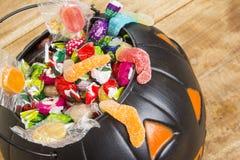 Zwarte plastic die pompoen met suikergoed op houten lijst wordt gevuld Royalty-vrije Stock Foto's