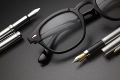Zwarte plastic oogglazen en vulpen stock fotografie