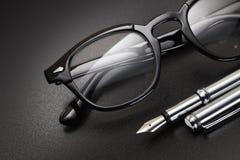 Zwarte plastic oogglazen en vulpen stock foto