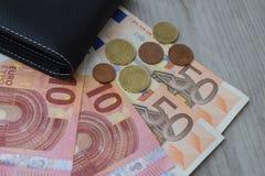 Zwarte portefeuille met euro muntbankbiljetten en muntstukken stock afbeeldingen