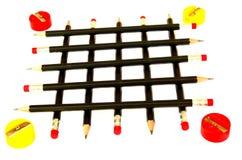 Zwarte potloden in een scherper met een net van geel en rood op de randen Stock Afbeeldingen