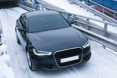 Zwarte prestigieuze auto op sneeuw stock afbeelding
