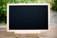Zwarte raad op houten lijstbovenkant met zon en onduidelijk beeld groene boom bokeh Royalty-vrije Stock Foto's