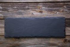 Zwarte raad van lei op oude rustieke houten achtergrond royalty-vrije stock afbeeldingen