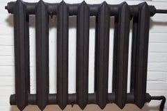 Zwarte radiator op witte bakstenen muur royalty-vrije stock foto's