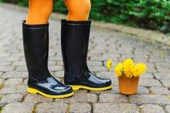 Zwarte regenlaarzen op de voeten van het kind stock afbeeldingen